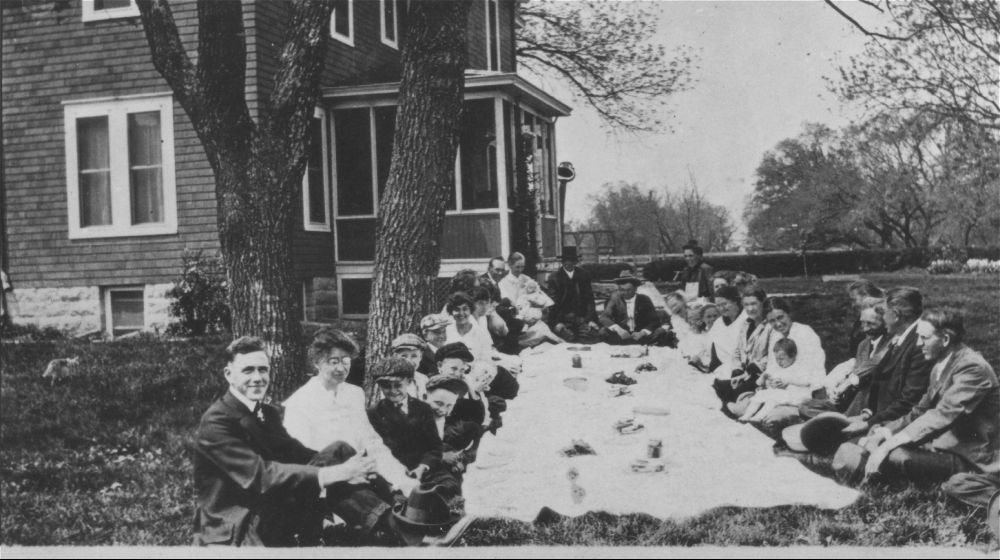 1915 – Irene, Wayne, Henry, George and Helen Rogler relaxing on the grass in front of their home.