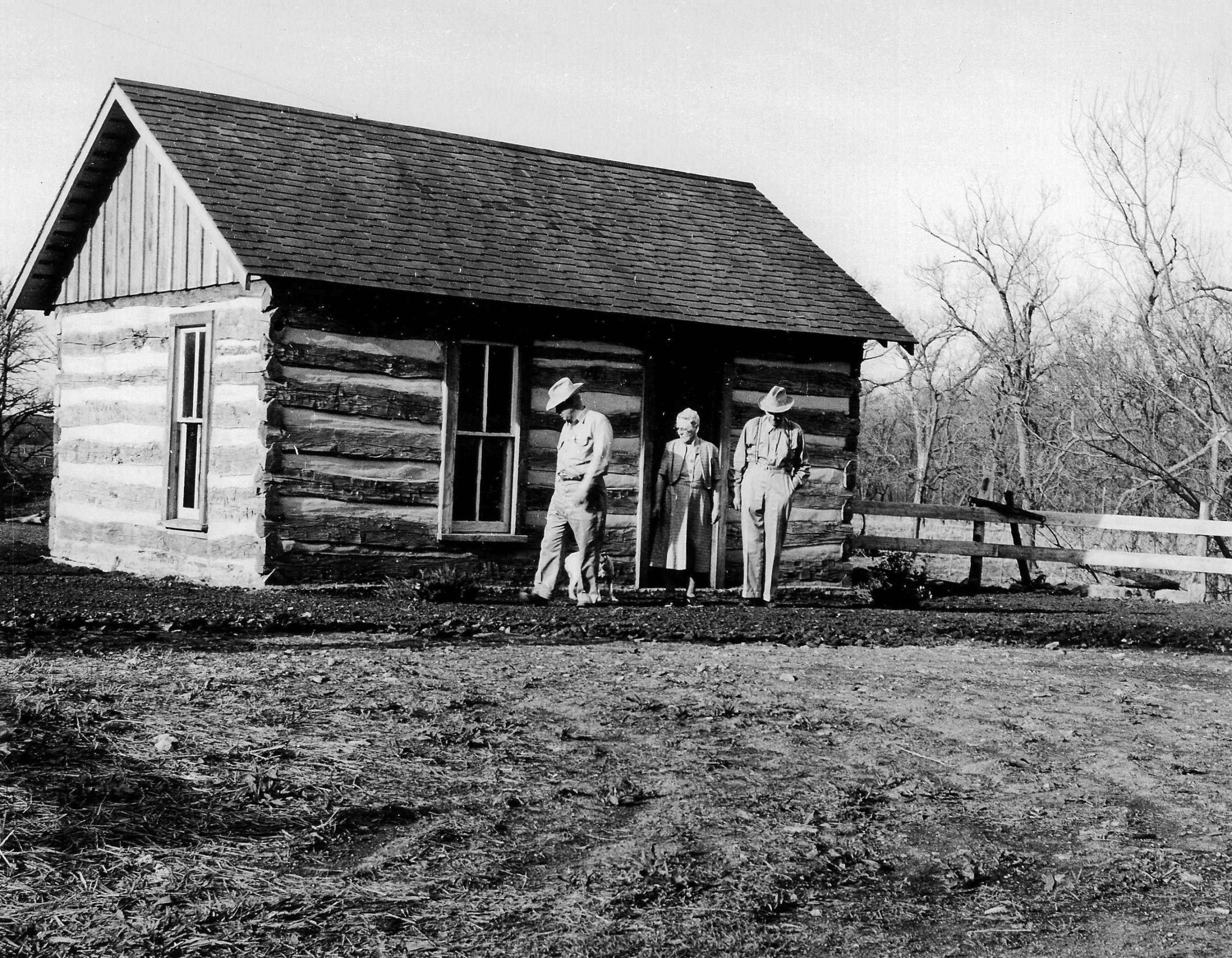 1960 – The Roglers inspect a log cabin moved in from another Rogler family's plot. The Commemorative Log Cabin was restored in 1960 from one of the original Rogler cabins built after the family settled in the area in 1859.