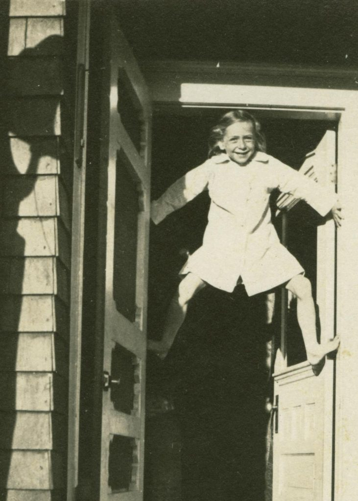 Irene Rogler, as a child, joyful braced in the doorway