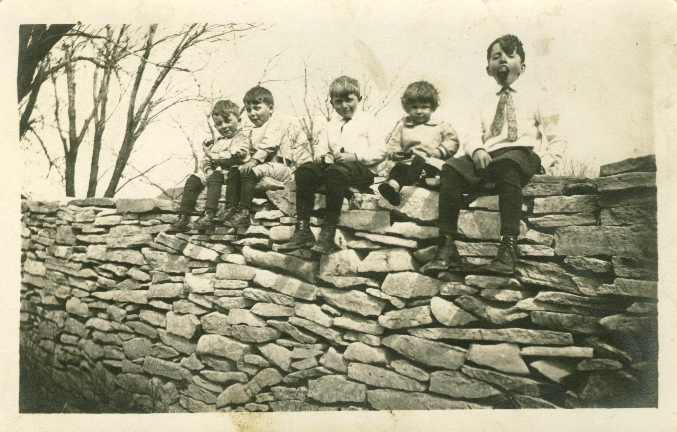 Children sitting on the stone fence