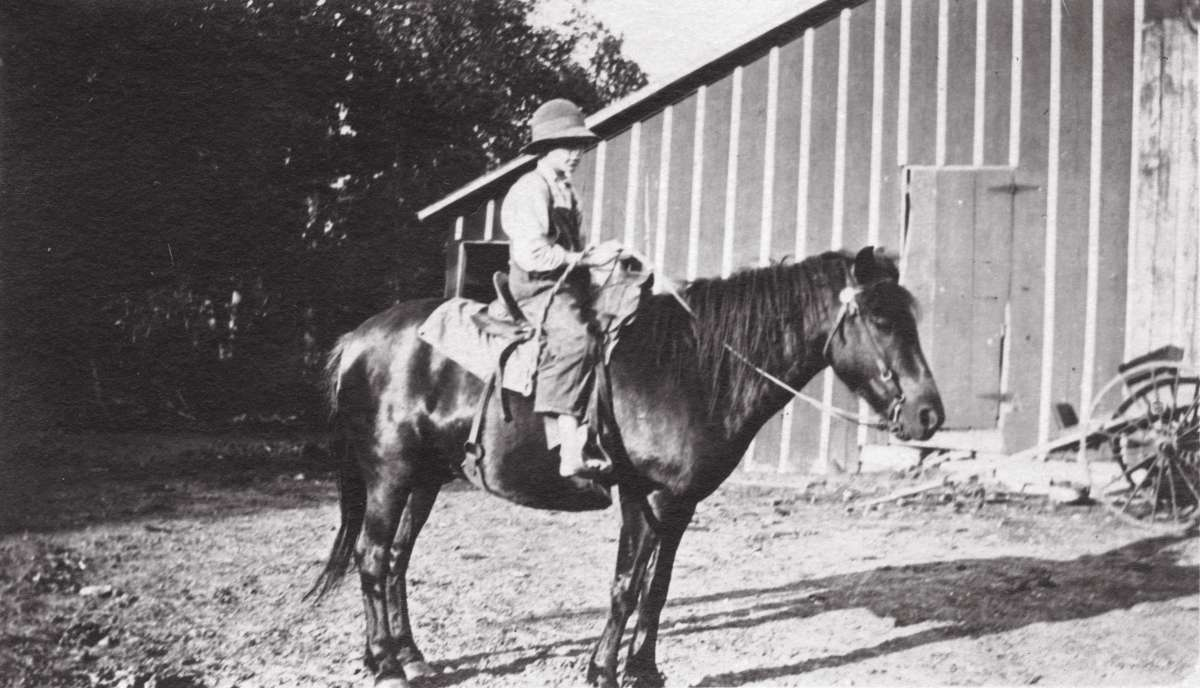 Irene on horseback in front of the old red barn